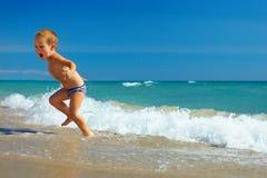 El niño lindo que se ejecuta del mar agita en la playa Fotografía de archivo