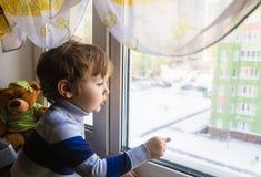 El niño mira hacia fuera la ventana Imagenes de archivo