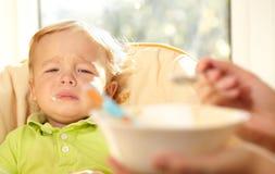 El niño muy disappointmented sobre las gachas de avena. Fotos de archivo libres de regalías