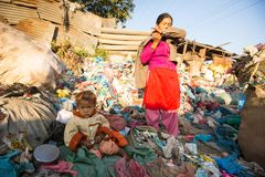 El niño no identificado se está sentando mientras que sus padres están trabajando en descarga, el 22 de diciembre de 2013 en Katm Foto de archivo libre de regalías