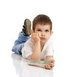El niño pequeño con el panel de control de la TV Fotos de archivo