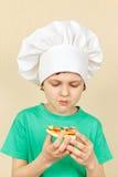 El niño pequeño en sombrero de los cocineros no le gusta gusto de la pizza cocinada Imagen de archivo libre de regalías