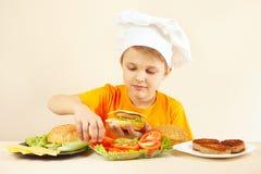 El niño pequeño en sombrero de los cocineros pone el tomate en la hamburguesa Foto de archivo