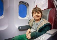 El niño pequeño feliz se sienta en asiento comercial del avión de reacción Fotografía de archivo libre de regalías