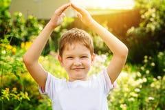 El niño pequeño que lleva a cabo su mano forma un tejado y simboliza el favorable Fotos de archivo libres de regalías