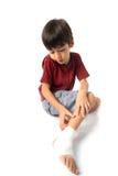 El niño pequeño tiene un accidente con su vendaje de la necesidad de la pierna para los primeros auxilios Imagen de archivo libre de regalías