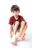 El niño pequeño tiene un accidente con su vendaje de la necesidad de la pierna para los primeros auxilios en el baclground blanco Fotografía de archivo libre de regalías