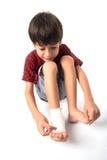 El niño pequeño tiene un accidente con su vendaje de la necesidad de la pierna para los primeros auxilios en el fondo blanco Imagen de archivo libre de regalías