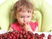 El niño prueba la cereza Fotografía de archivo libre de regalías