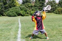 El niño que juega a lacrosse grita en alegría de la celebración mientras que se sostiene Fotografía de archivo