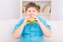 El niño rechoncho está comiendo una hamburguesa Fotos de archivo