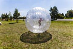 El niño se divierte en la bola de Zorbing Imagen de archivo