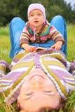 El niño se sienta en la madre, que miente en hierba Foto de archivo libre de regalías