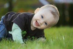 El niño se sienta y riendo en la hierba Imagen de archivo libre de regalías