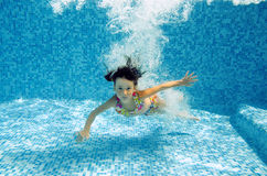 El niño subacuático feliz salta a la piscina Imagen de archivo