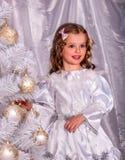 El niño y adorna el árbol de navidad blanco Imagenes de archivo