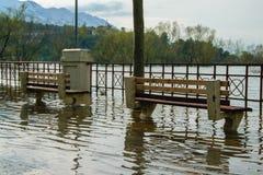 El nivel del agua aumentado del río llega en la acera imagenes de archivo