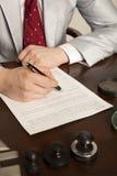 El notario firma los documentos de nuestra oficina fotografía de archivo