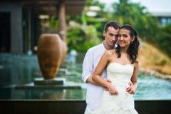 El novio abraza a la novia contra el interior hermoso con una piscina en verano fotografía de archivo libre de regalías