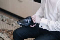 El novio ata los cordones en sus zapatos Foto de archivo libre de regalías
