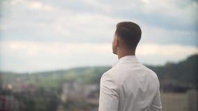 El novio atractivo en el traje blanco está viniendo en la terraza y está disfrutando del paisaje encantador solamente almacen de video