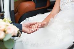 El novio ayuda a la novia a salir del coche foto de archivo