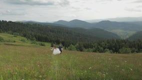 El novio con la novia va para una comida campestre en las colinas de una montaña Pares de la boda Familia metrajes