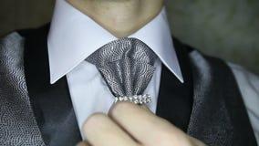el novio corrige la broche en la corbata de plata oscura metrajes