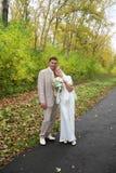El novio de los jóvenes abraza a su novia en parque del otoño Fotografía de archivo