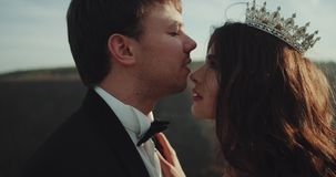 El novio de los pares y la novia hermosos en el medio del paisaje preparan besar a su novia almacen de metraje de vídeo