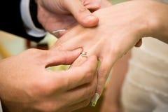 El novio desgasta un anillo de diamante sobre la mano de las novias Foto de archivo