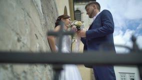 El novio elegante hermoso en el ramo azul del traje y de la boda de rosas coloridas está viniendo a su novia encantadora con bast almacen de video