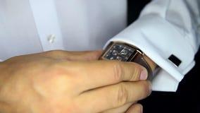 El novio en camisa ajusta el reloj presta la atención al primer del tiempo