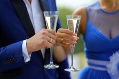 El novio en un traje azul y la novia en un vestido azul que se coloca con los vidrios en los cuales se vierte el champán Imagen de archivo
