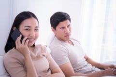 El novio enojado escucha la novia que habla en el teléfono Fotografía de archivo libre de regalías