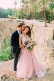 El novio está besando a su novia Abarcamiento feliz de los recienes casados El hombre en smoking y mujer en un vestido de boda ro Fotografía de archivo
