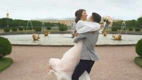 el novio está circundando a la novia en el jardín almacen de video