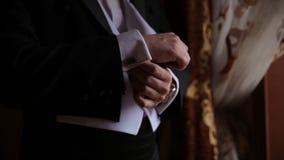 El novio está llevando a cabo las manos en el lazo, casandose el traje Ciérrese para arriba de un hombre de la mano cómo lleva la Fotografía de archivo