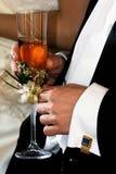 El novio está sosteniendo un champán de cristal En los vínculos de puño de los puños Fotos de archivo