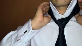 El novio Fastens Shirt Collar aprieta el primer oscuro del lazo