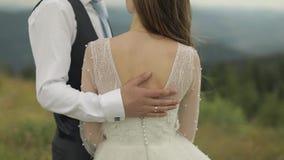 El novio frota ligeramente la parte posterior de la novia cerca de las colinas de la montaña Pares de la boda almacen de metraje de vídeo