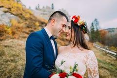 El novio hermoso en traje azul elegante que abrazaba blanco vistió a la novia que sostenía el ramo de rosas en paisaje natural id Foto de archivo