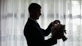 El novio hermoso fija su ramo que se casa cerca de ventana Silueta almacen de video