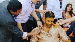 El novio indio ríe mientras que los hombres lo pintan con goma de la cúrcuma almacen de video