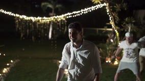 El novio lanza la liga en la boda Partido de la celebración en la isla tropical metrajes