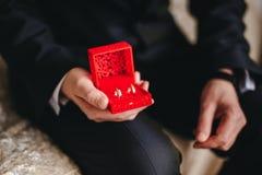 El novio lleva a cabo el anillo en su mano imagen de archivo libre de regalías