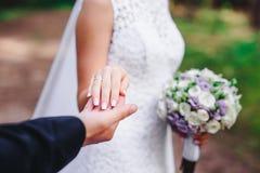 El novio lleva a cabo la mano de la novia foto de archivo libre de regalías