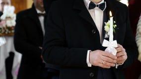 El novio lleva a cabo una vela en la iglesia Ceremonia de boda del cristianismo metrajes