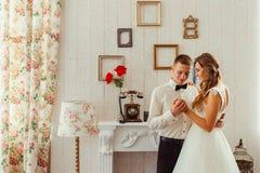 El novio mira con amor el bride& x27; manos de s Foto de archivo libre de regalías