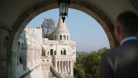 El novio mira a la novia que se está colocando en el balcón del castillo viejo metrajes